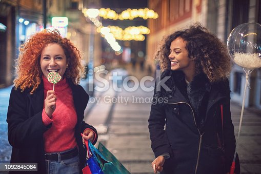 Young beautiful women having fun while shopping together presents for Christmas