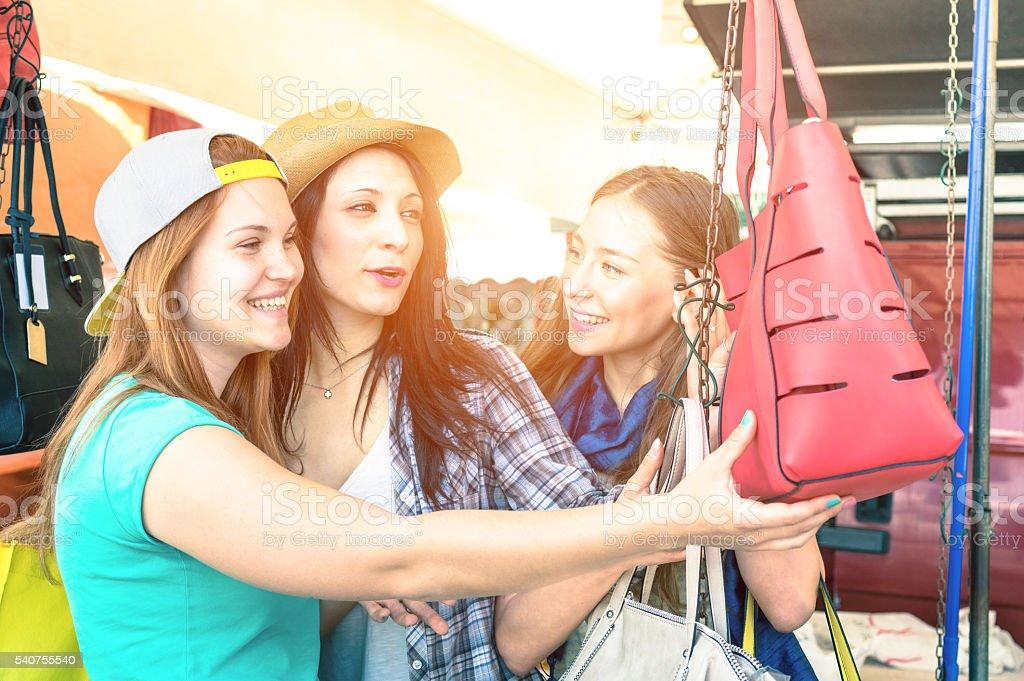 Young beautiful women girlfriends at flea market looking bags stock photo