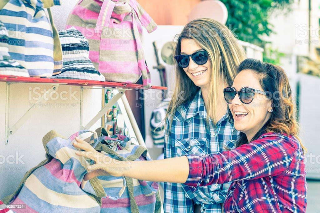 Young beautiful women girlfriends at flea market looking for bag stock photo