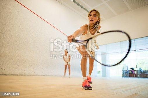Young beautiful women playing squash at the club