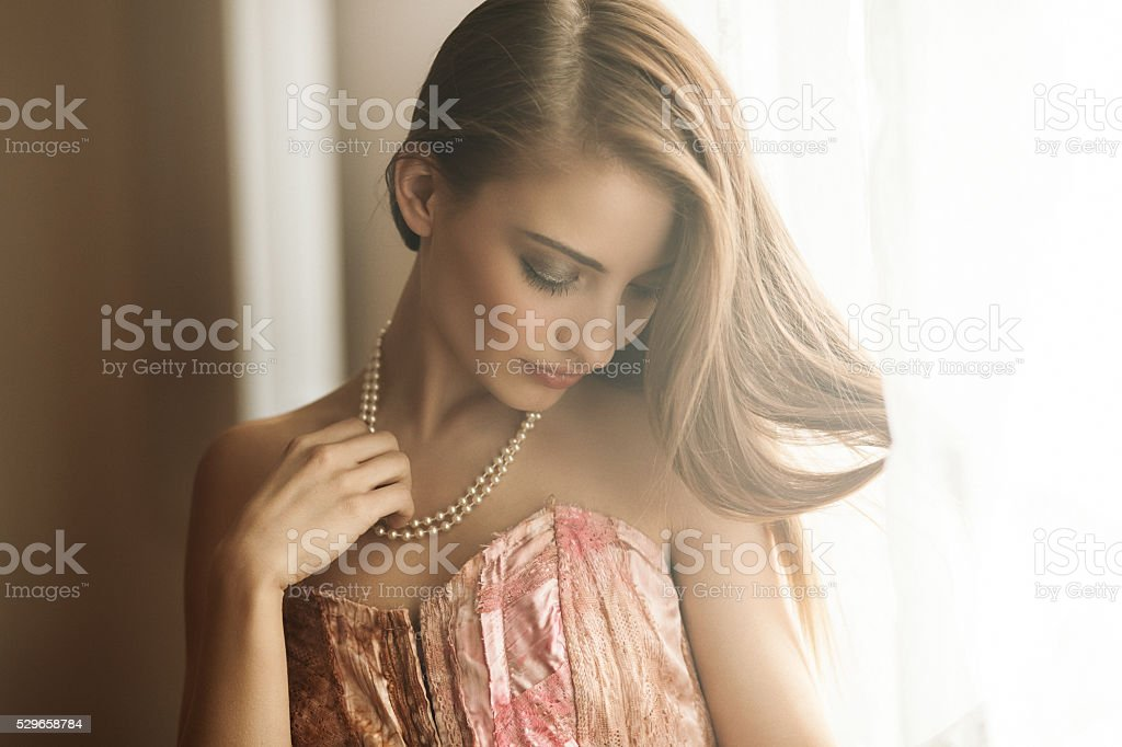 young beauty by the window stock photo