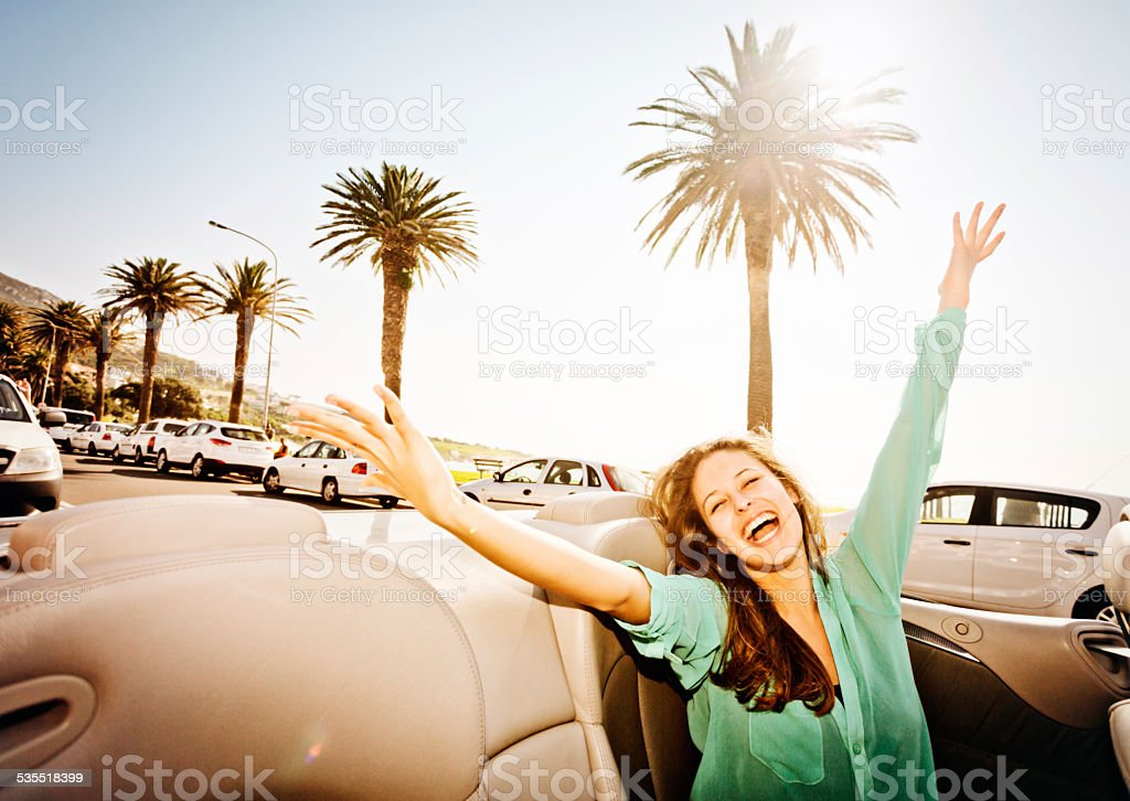 Young beauty in convertible driving on seaside promenade waves delightedly stock photo