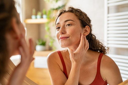 Beauty girl looking at mirror while touching her face and checking pimple, wrinkles and bags under the eyes, during morning beauty routine. Smiling pretty woman applying cream on her face in bathroom. Happy smiling beautiful young woman applying moisturizer.