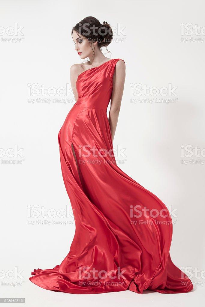 554569477de4 Bellezza giovane donna in svolazzanti Vestito rosso. Sfondo bianco. foto  stock royalty-free