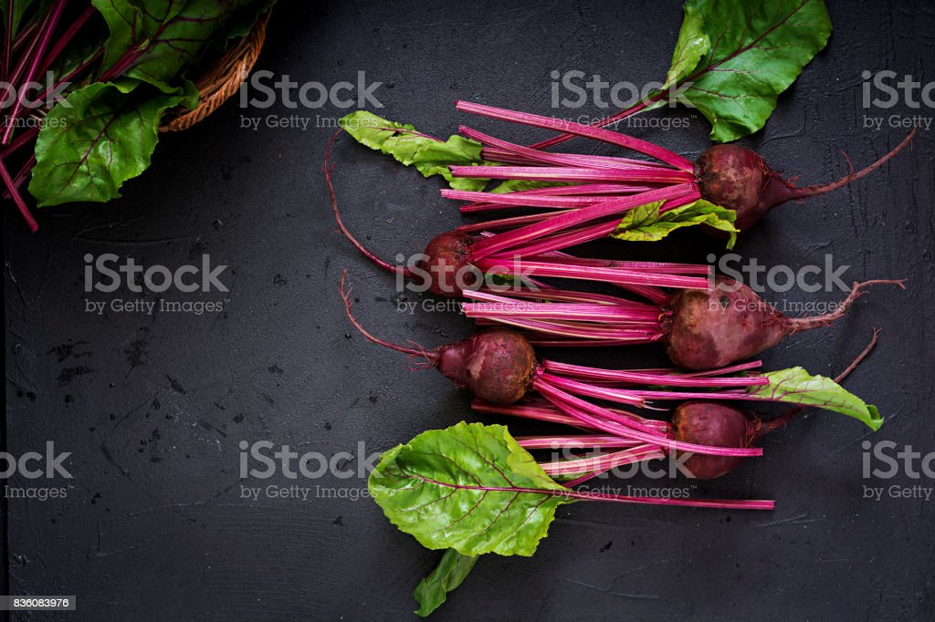 Young beetroot with a tops on a dark background. Flat lay. Top view. stock photo