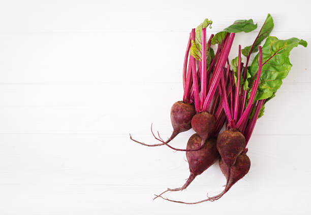 Young beetroot with a tops on a white background. Flat lay. Top view stock photo