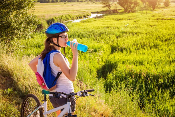 Young bicyclist drinking water by the river Young bicyclist drinking water by the river at sunset female biker resting stock pictures, royalty-free photos & images