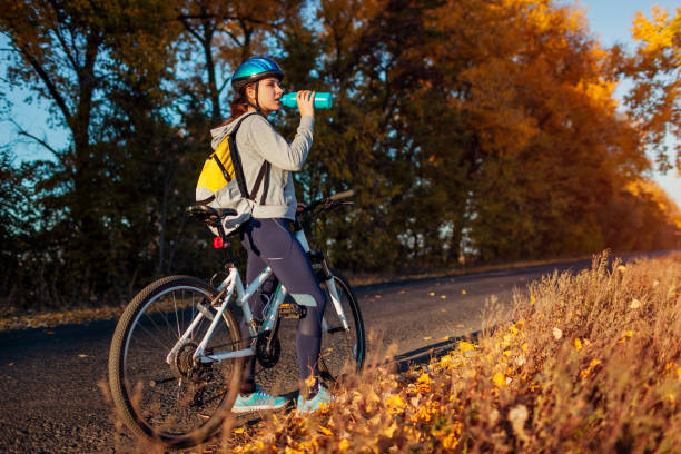 Young bicyclist having rest after a ride in autumn field at sunset. Woman drinking water on road Young bicyclist having rest after a ride in autumn field at sunset. Woman drinking water on road. Healthy lifestyle female biker resting stock pictures, royalty-free photos & images