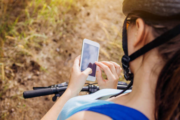 Young bicyclist searching for the right way using a navigator Young bicyclist searching for the right way using a navigator on her phone female biker resting stock pictures, royalty-free photos & images