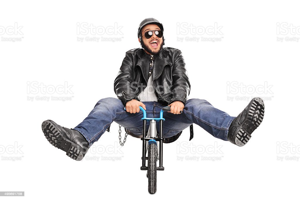 Young biker riding a very small bicycle and smiling stock photo