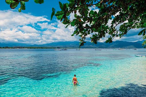 istock Young bikini woman relax in blue ocean on tropical island 1163300301