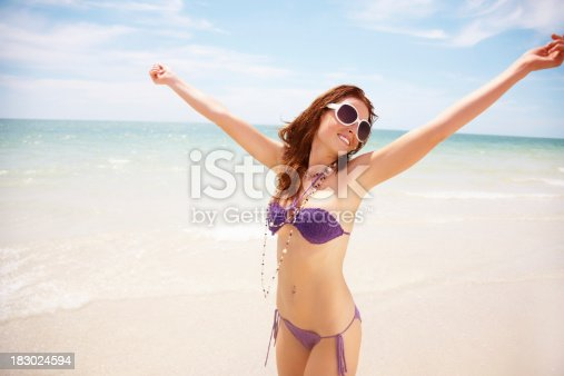 Portrait of a young bikini female with her hands stretched out on beach