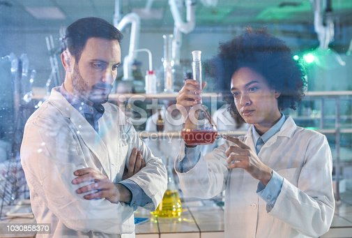 499203366istockphoto Young biochemists analyzing liquid while working in laboratory. 1030858370
