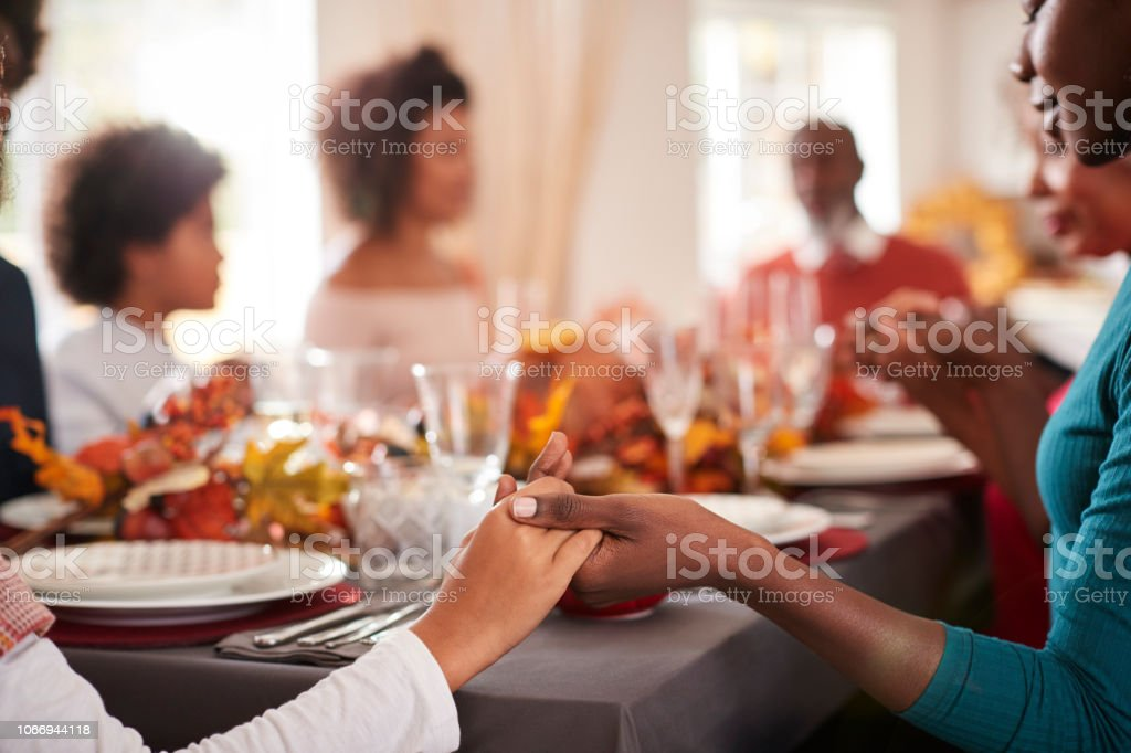 Young black adult woman and her daughter holding hands and saying grace with their multi generation family at the Thanksgiving dinner table, detail, focus on foreground - Zbiór zdjęć royalty-free (20-29 lat)