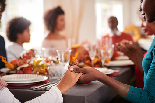 Young Black Adult Woman And Her Daughter Holding Hands And Saying Grace With Their Multi Generation Family At The Thanksgiving Dinner Table Detail Focus On Foreground - zdjęcia stockowe i więcej obrazów 20-29 lat
