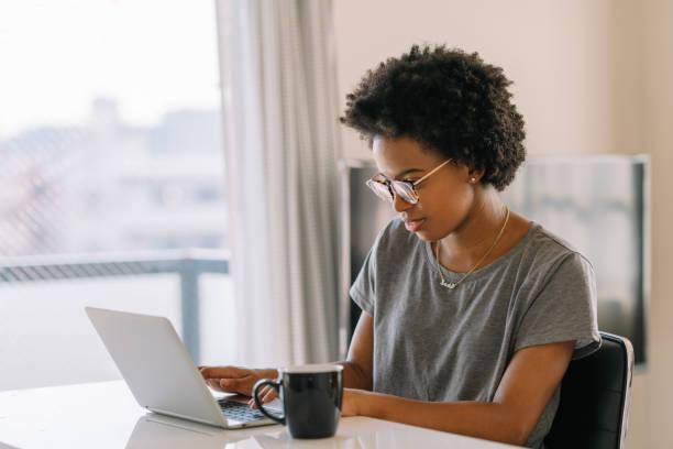 年輕的 黑色美麗的女人使用筆記本電腦在家裡 - small business saturday 個照片及圖片檔