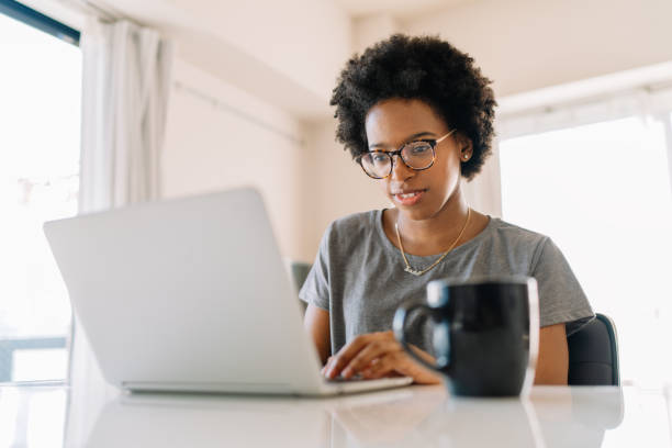 Young black beautiful woman using laptop at home stock photo