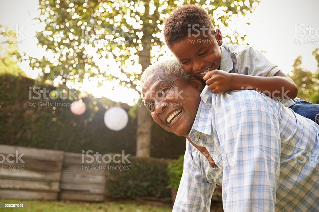 Young black boy climbing on his grandfather's back in garden stock photo