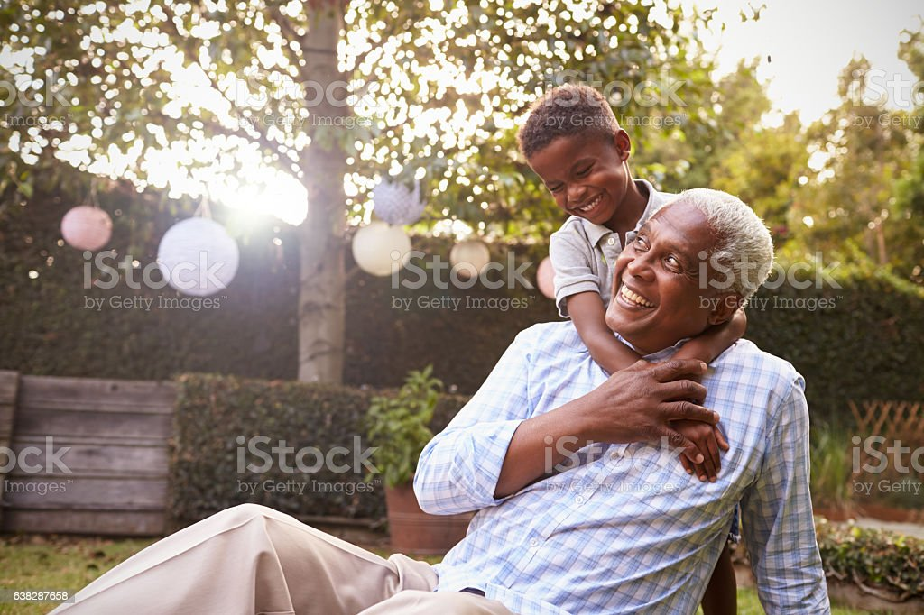 Young black boy embracing grandfather sitting in garden stock photo