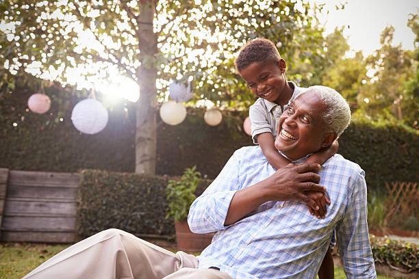 Young black boy embracing grandfather sitting in garden - foto de acervo