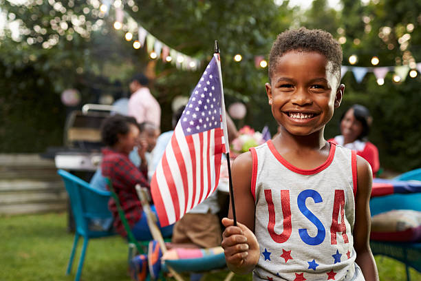 young black boy holding flag at 4th july family garden - fourth of july fotografías e imágenes de stock
