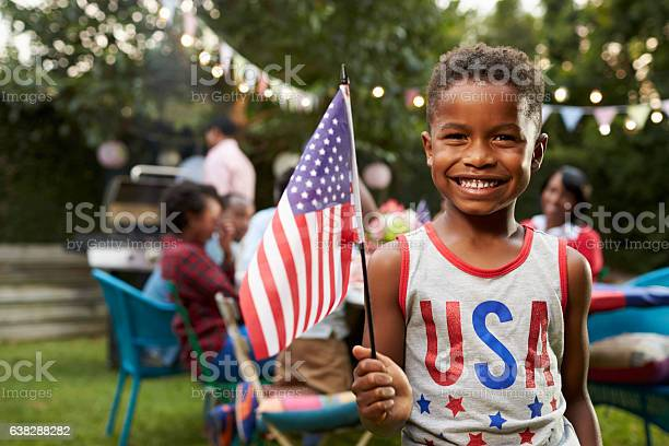 Young Black Boy Holding Flag At 4th July Family Garden Stock Photo - Download Image Now
