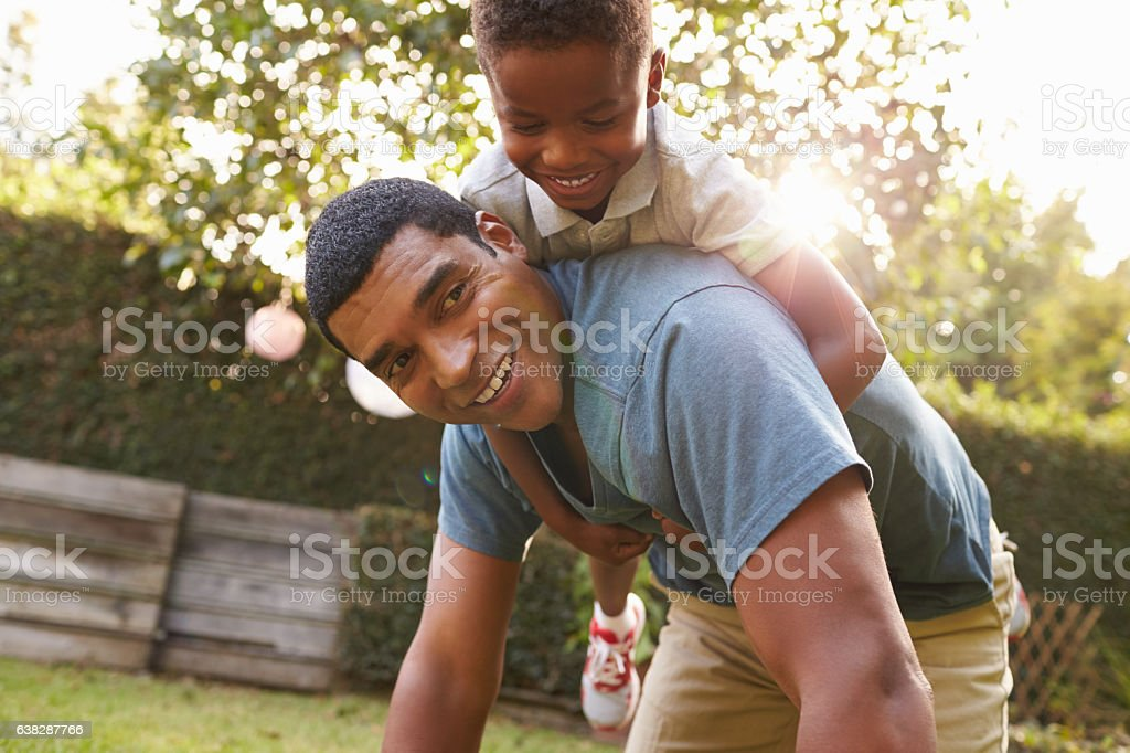 Young black boy playing on dad's back in a garden stock photo