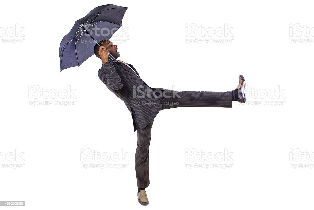 Young Black Businessman Dancing with Umbrella stock photo
