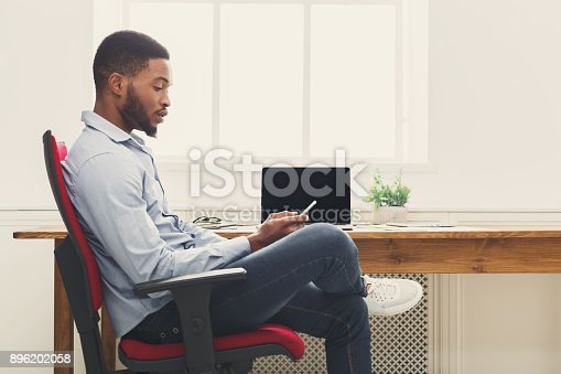 istock Young black businessman using mobile phone 896202058