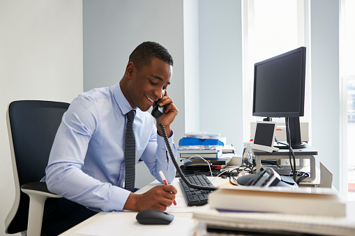 Young black businessman using the phone at his office desk