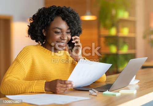 Young black smiling businesswoman talking to colleagues by phone, working with laptop at cafe