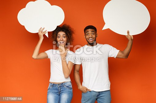 istock Young black couple holding communication bubbles at studio 1127568144