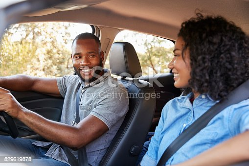 829619540 istock photo Young black couple in a car looking at each other smiling 829619878