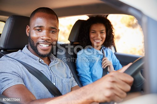 829619540 istock photo Young black couple in a car on a road trip smiling to camera 829622044