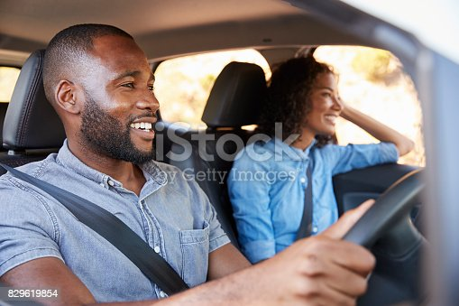 829619540 istock photo Young black couple in car on a road trip look ahead smiling 829619854