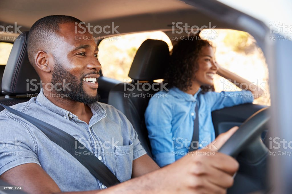 Young black couple in car on a road trip look ahead smiling stock photo