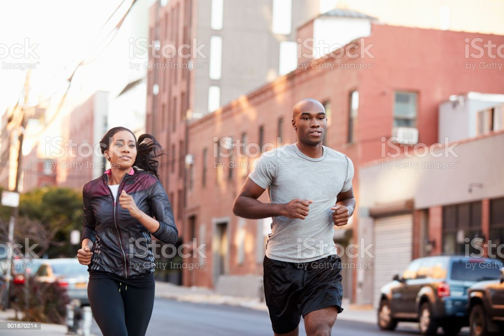 Young black couple jogging in Brooklyn street, close up stock photo
