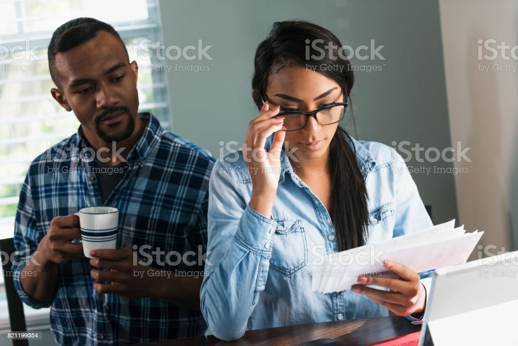 Young black couple paying bills on computer stock photo