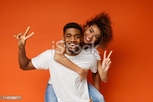 Millennial african-american man and woman playing piggyback ride, showing peace gesture on orange background, panorama