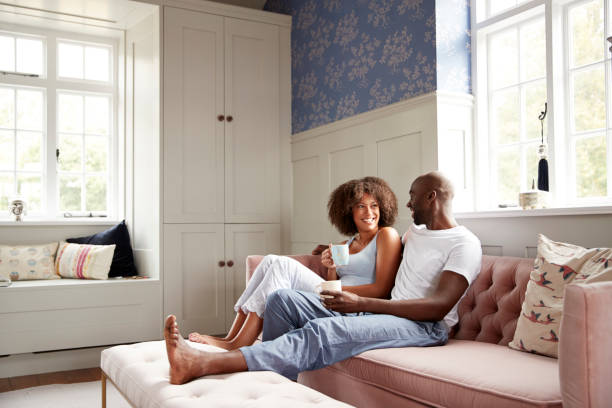 Young black couple sitting together on couch in living room drinking coffee and talking in the morning, low angle, full length stock photo