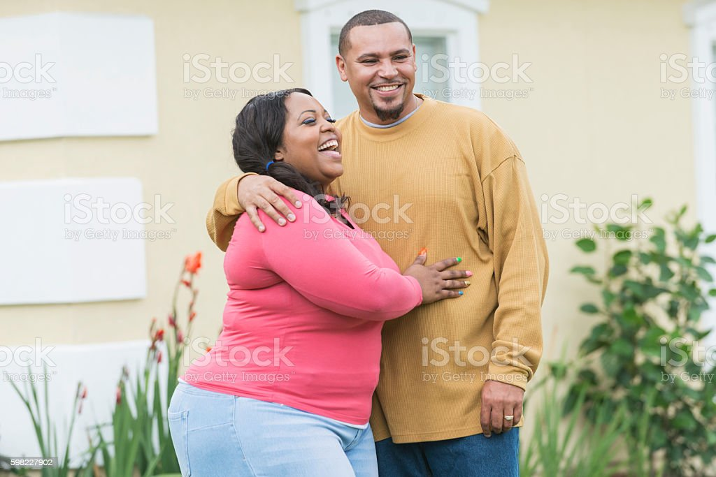 Young black couple standing outside home stock photo