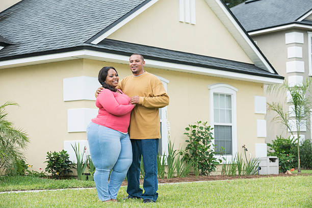 young black couple standing outside home - damen jeans übergrößen stock-fotos und bilder