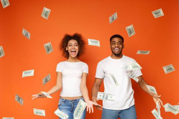 Young black couple standing under money banknotes shower stock photo