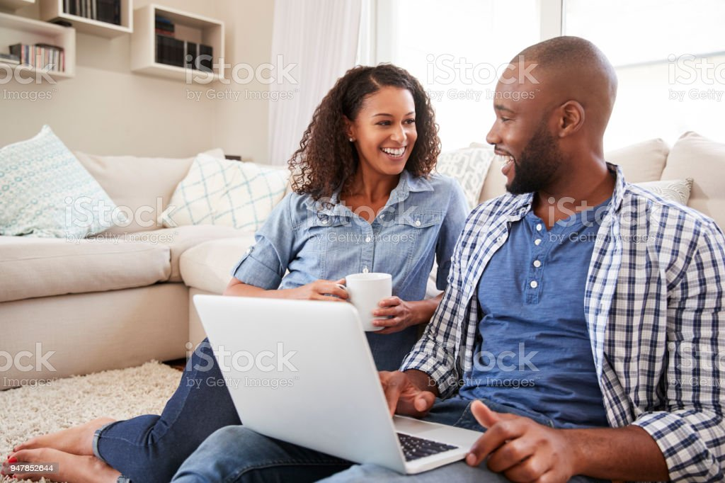 Young black couple using laptop at home look at each other stock photo