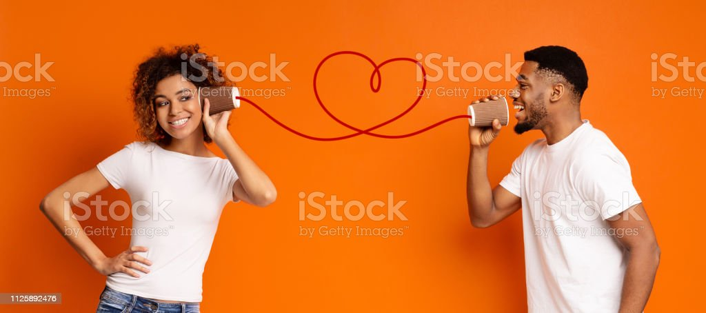 Young black couple with can phone on orange background royalty-free stock photo