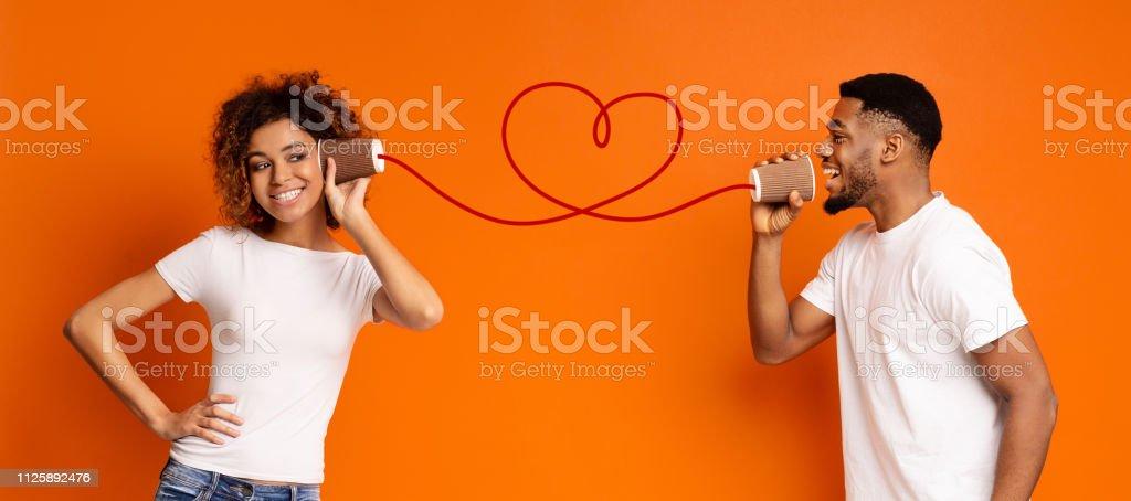 Joven pareja negra con puede llamar sobre fondo naranja foto de stock libre de derechos