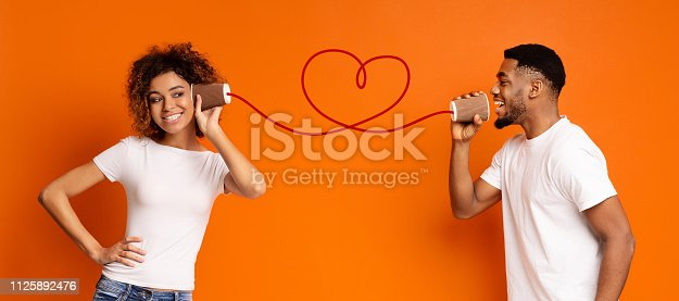 Communication and fun. Young black couple talking through tin can phone, orange background, panorama