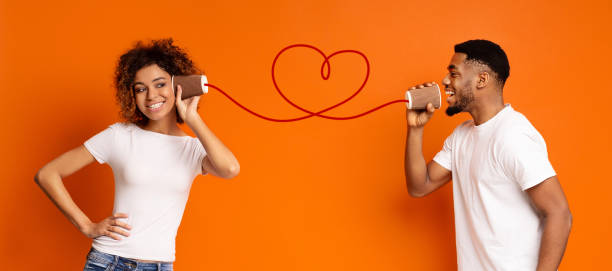 Young black couple with can phone on orange background stock photo