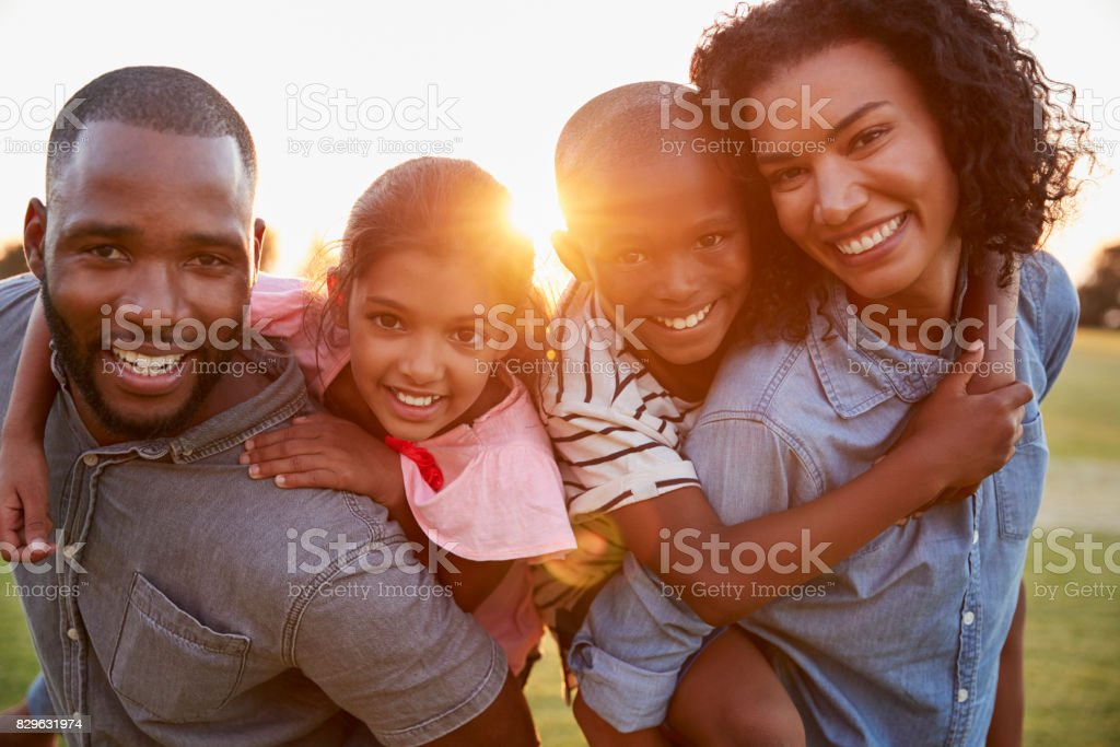 Young black couple with children on piggyback stock photo