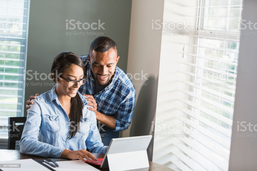 Young black couple, woman on computer paying bills stock photo